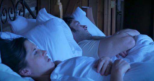 Attractive young woman and man arguing while lying in bed sighing and acting stubborn refusing to Live Action