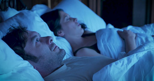 Man tossing and turning in bed unable to sleep expressing extreme frustration over his insomnia and GIF