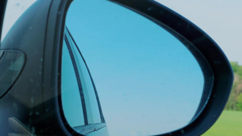 Sky reflection in right side rear view mirror at car driving Live Action