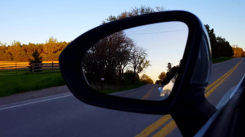 Driving Rural Road View of Side Mirror at Sunset. Driver Point of View POV Looking Down Side View Footage