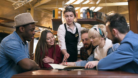 Cute young waitress helping with order to young company of multi ethnic friends Footage