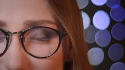 Closeup half face portrait of young pretty caucasian girl in glasses looking at Footage