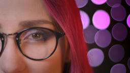 Closeup half face portrait of young pretty caucasian girl with red dyed hair in Footage