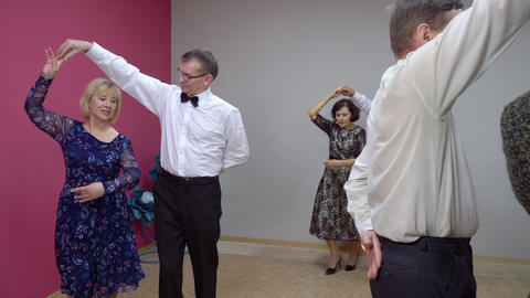 Elegant elderly pairs are dancing polonaise. Dance class for senior people Live Action