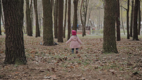 Beautiful little girl walking alone in the forest Footage