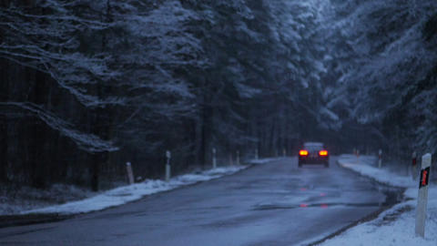 The car is moving along a winter forest road in the evening Footage