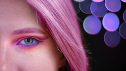 Closeup half face shoot of young attractive caucasian female with pink beautiful Footage