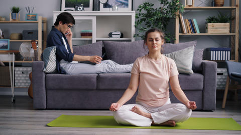 Young lady meditating in lotus position while guy talking on phone using laptop Footage