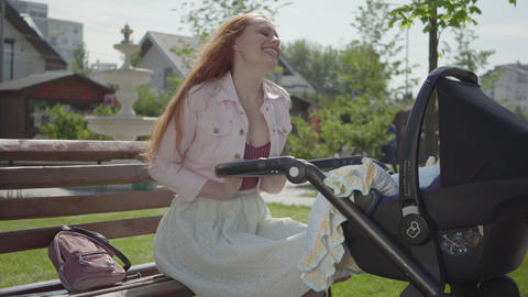Beautiful positive red-haired woman smiling looking in the pram in the park Footage
