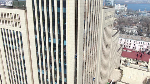 The side of a big office building with a worker cleaning windows on the side Live Action