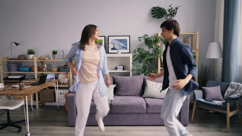 Girl and guy happy youth dancing at home relaxing and laughing enjoying life Footage