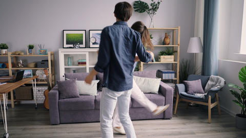 Girl and guy happy youth dancing at home relaxing and…, Live Action