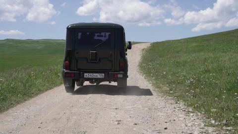 SUV rides on the dusty road in nature Live Action