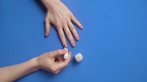 Woman paints her nails with transparent protective nail polish on the background ビデオ