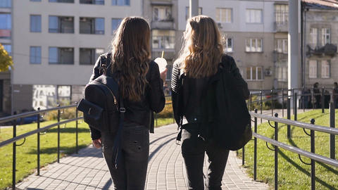 View rear of two stylish young girlfriends with long hair and stylish backpacks Live Action