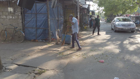 Kataragama, Sri Lanka - 2019-03-29 - Man Sweeps Leaves and Loose Dirt From His Footage