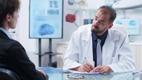 Caucasian doctor in modern office with research equipment taking notes from a Footage