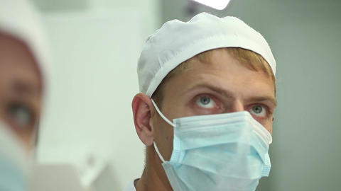intern closely watching the progress of the operation on the monitor of doctor Footage