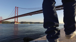 Man walking relaxing at the river Tagus with the bridge 25 to April Lisbon 4k Footage