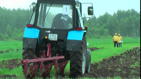 Tractor operator plows the site in rain Footage