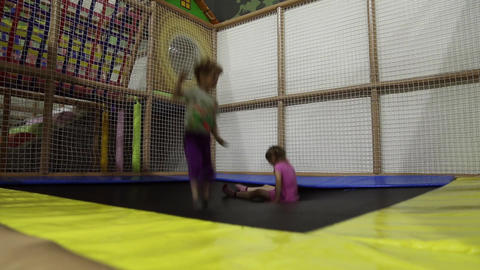 A girl and a boy are jumping on a trampoline Footage