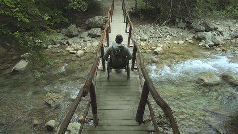 Man In Wheelchair On Footbridge In The Mountains Footage