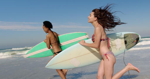 Young female friends running with surfboard 4k Live Action
