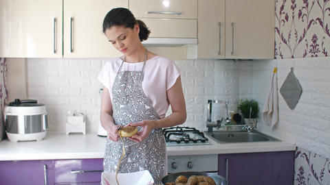 Woman peeling potatoes at kitchen Footage