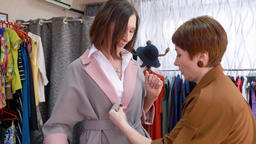 Adult woman trying new coats in fashion store while shopping. Stylish woman Footage
