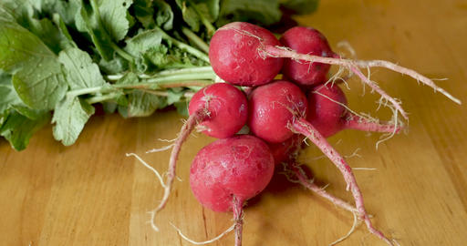 Push in of fresh organic in season rad radishes with their greens on a wooden cutting board Footage