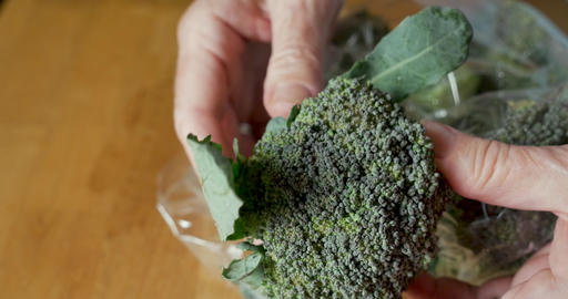 Hand pulling an organic fresh seasonal broccoli floret out of a plastic bag purchased from a farmers Footage