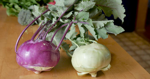 Two varieties of fresh, ripe, organic purple and white kohlrabi vegetables on a wooden cutting board Footage