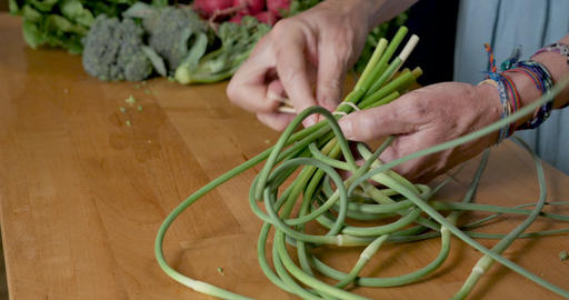 Hand removing a rubber band from a bunch of garlic scapes on a cutting board with a variety of other GIF