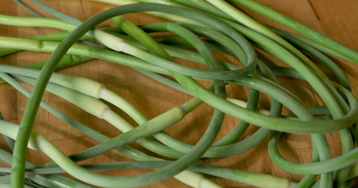 Overhead shot of a bunch of organic, fresh, seasonal, spring, garlic scapes on a wooden cutting Footage