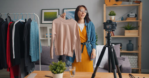 Female stylist recording video for online blog showing trendy clothes talking Live Action