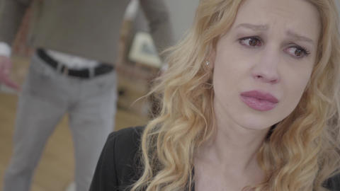 Pretty blond woman in the foreground crying, an emotional angry man yelling and Footage