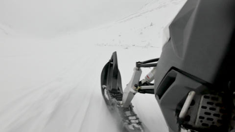grey snowmobile speeds along snowy slopes among mountains Footage