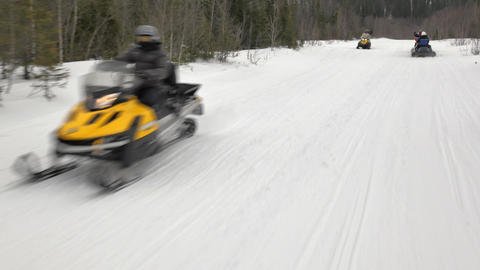 camera goes past speeding snow scooters with profeccionals Footage