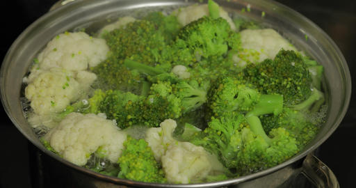 Cooking colorful broccoli and cauliflower in the pan with boiling water Live Action