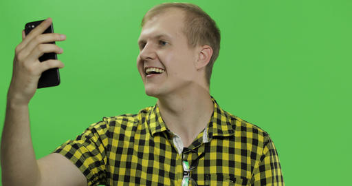 Caucasian young man in yellow shirt using mobile phone for video call Footage