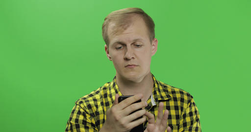 Caucasian man in yellow shirt scrolling, texting on the smartphone in his hands Footage