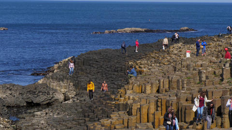 People climb on the rocks of the famous Giants Causeway in Northern Ireland - Footage