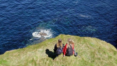Two girls in Ireland walk on the cliffs of Kilkee on a sunny day - aerial drone Live Action