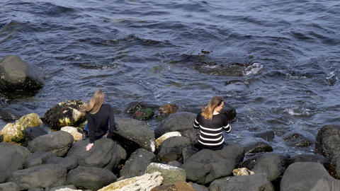 Two girls sit on the rocks at the Causeway Coast in Northern Ireland Footage
