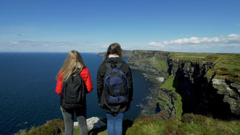 Two young women enjoy the panoramic view at the Cliffs of Moher in Ireland Live Action