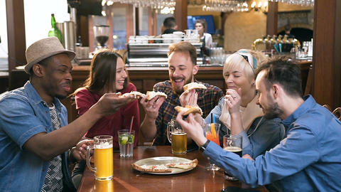 Company of five young hipster friends clinking peace of pizza in the stylish bar Live Action