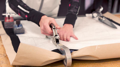 Dressmaker designer stapling and cutting fabric pattern at garment industry Live Action