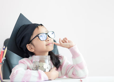 Little Asian girl wearing graduate hat putting the coin into clear glass jar 017 フォト