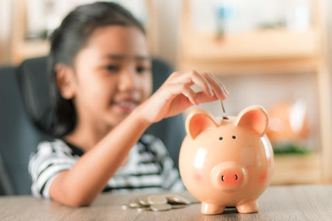 Asian little girl in putting coin in to piggy bank 0008 フォト