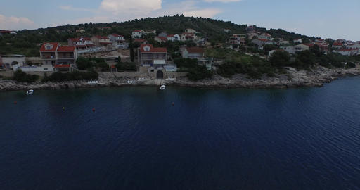 Aerial drone scene of rocky coastline with houses at the shore. Camera goes clos Footage